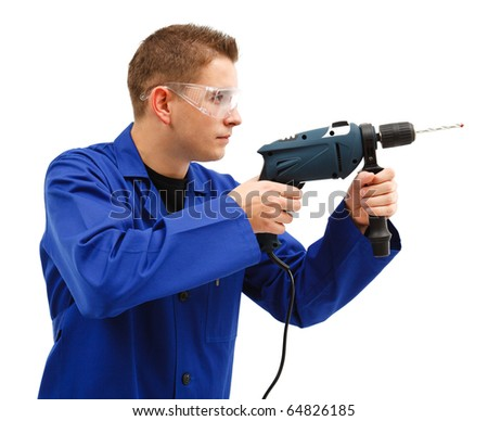Young man drilling with drill machine and wearing protective glasses - stock photo