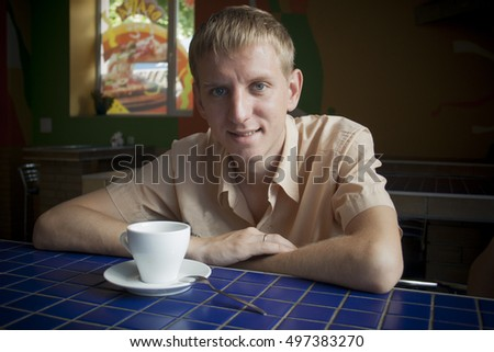 Young man drinking a tea at the cafe