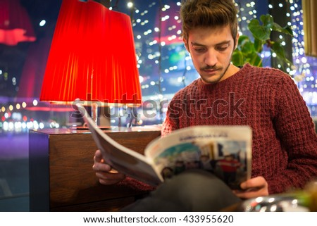 Young man drinking coffee and reading news on sofa - stock photo