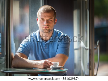 Young man drinking coffee in a cafe - stock photo