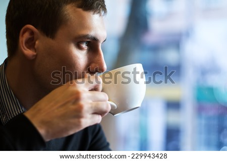 Young man drinking coffee in cafe - stock photo