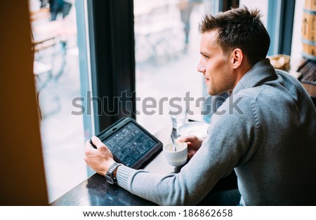 Young man drinking coffee in cafe and using tablet computer - stock photo
