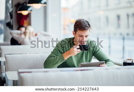 Young man drinking coffee on the street while using tablet computer