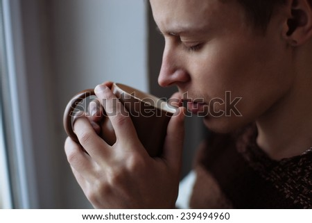 Young man drinking cup of coffee  - stock photo