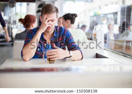 Young man drinking his problems away in a cafe - stock photo