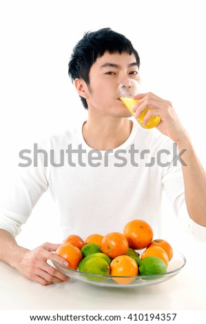 Young man drinking juice holding with fruit in bowl
