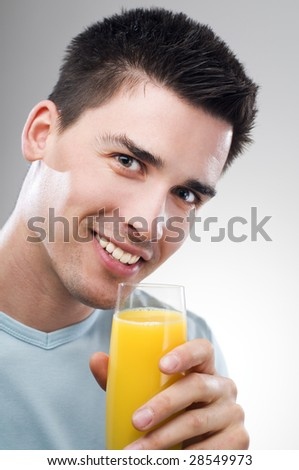 young man drinking orange juice close up - stock photo