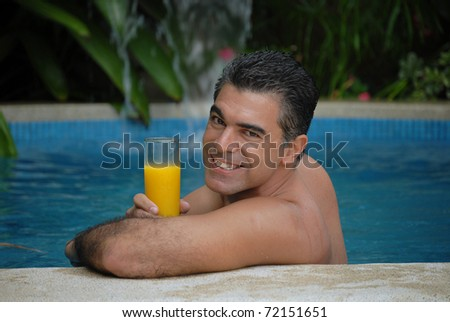 Young man drinking orange juice in a swimming pool. - stock photo