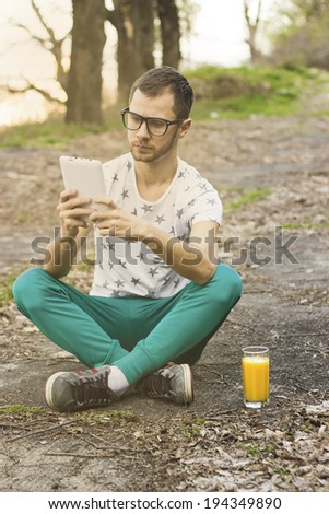 Young man drinking orange juice outdoor while looking at tablet