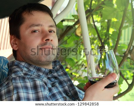 Young man drinking red wine outdoor background and looking calm. Closeup portrait - stock photo