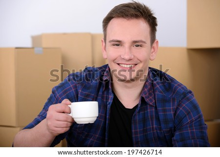 Young man, drinking tea, unpacking boxes moving to a new home - stock photo