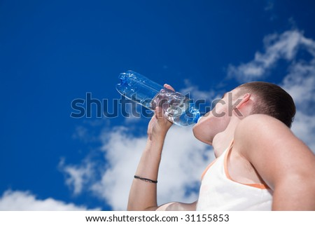 young man drinking water against cloudy sky