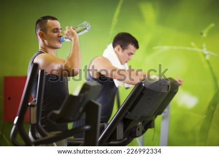 Young man drinking water during practice at the gym - stock photo