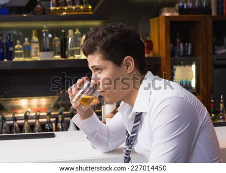 Young man drinking whiskey neat at the bar - stock photo