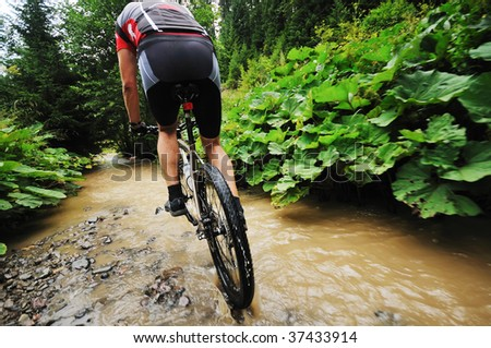 young man drive mountain bike over water river - stock photo