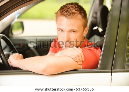 Young man-driver in red clothes at wheel car.