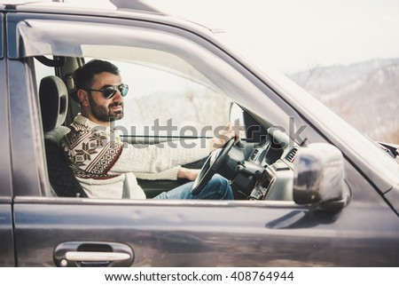 Young man drives a car in mountains. Travel and adventure concept. - stock photo