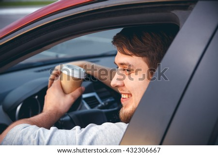 Young man driving a car  drinks hot, morning coffee