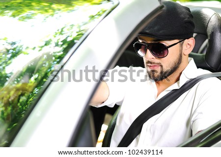 Young man driving a car with - stock photo