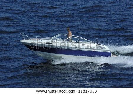 Young man driving a motor boat at ocean in the sun - stock photo