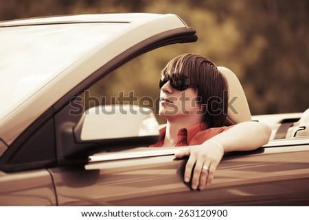 Young man driving convertible car - stock photo