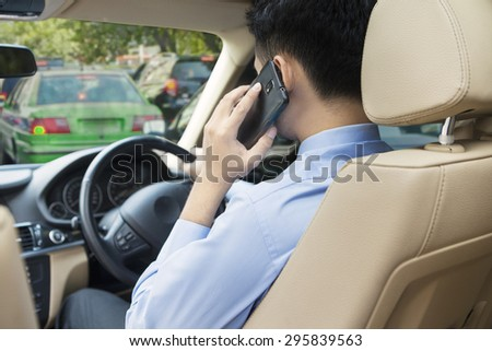 Young man driving his car on the traffic jam while speaking on the cellphone