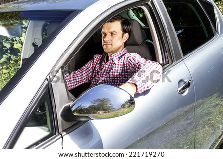 Young man driving his new car  - stock photo
