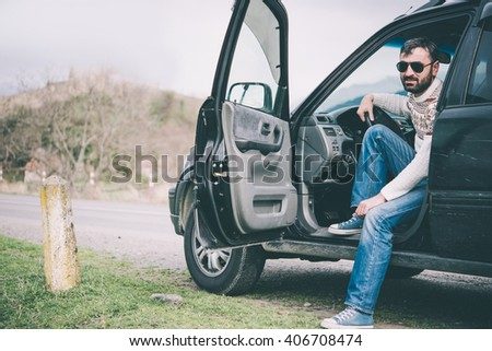 Young man driving the car in the mountains is relaxing at a roadside