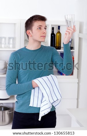 young man drying and polishing glass with a kitchen towel