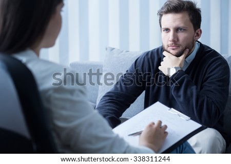 Young man during therapy at psychologist's office - stock photo