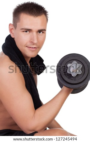 Young man during workout with dumbbells, looking at camera