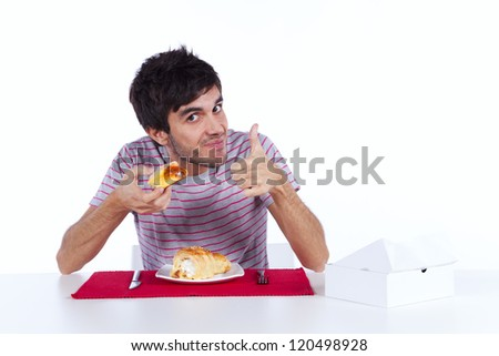 Young man eating a cake with lots of cream - stock photo