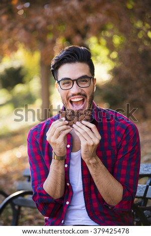 Young man eating a cookie, looking happy at the camera. Hipster style, wearing a check shirt - stock photo