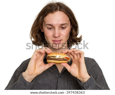Young man eating a hamburger from fast food, isolated on white