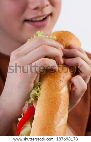 Young man eating a healthy baguette sandwich