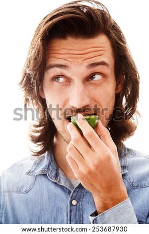 Young man eating a lime, face portrait on white background - stock photo