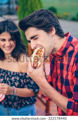 Young man eating an american hot dog and woman laughing on the background in a outdoors summer barbecue with his friends - stock photo