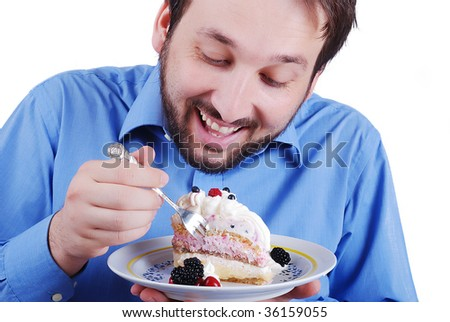 Young man eating colorful cake, isolated - stock photo