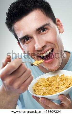 young man eating corn flakes close up - stock photo