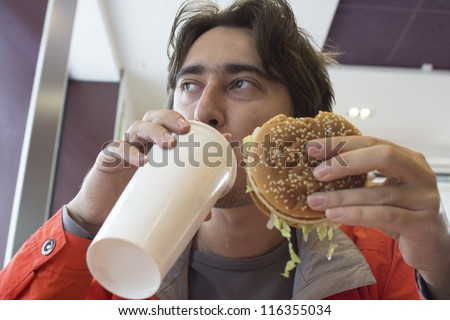 Young man eating fast food - stock photo