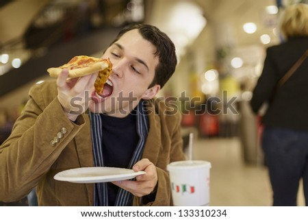 Young Man Eating Pizza At The Food Court In A Mall - stock photo