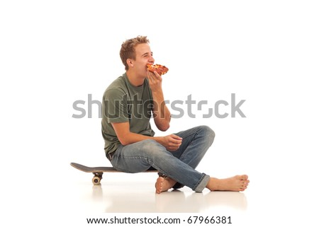 Young man eating pizza while sitting on skateboard - stock photo