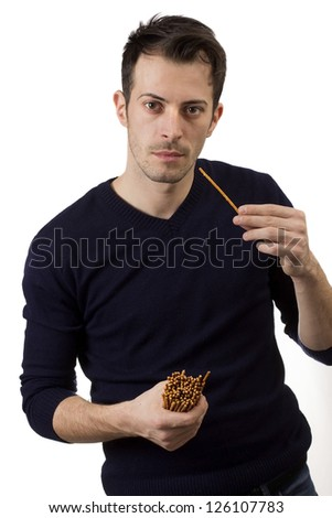 Young man eating salty sticks isolated over white background