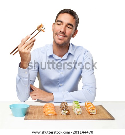 Young man eating sushi - stock photo