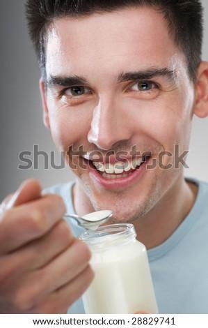 young man eating yogurt close up shoot - stock photo