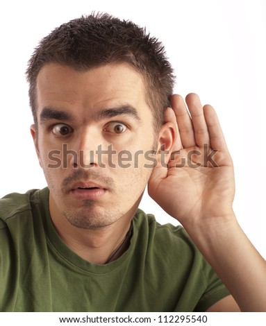 Young man eavesdropping and making funny facial expression - stock photo