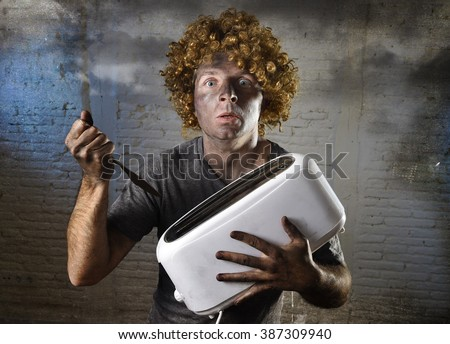 young man electrocuted trying to get toast out of toaster with knife suffering domestic accident with dirty burnt face in funny shock expression screaming crazy in electricity danger concept - stock photo