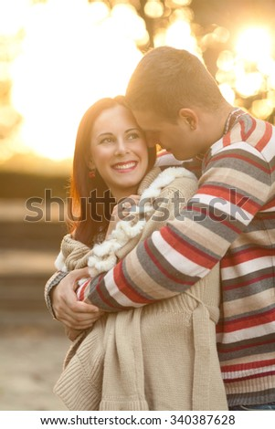 Young man embracing his beautiful smiling girlfriend while walking in a park - stock photo