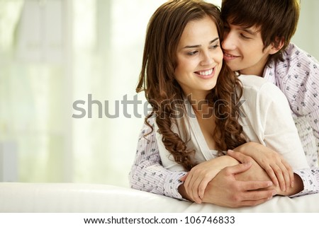 Young man embracing his happy girlfriend or wife
