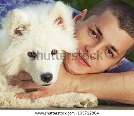 Young man embracing solid white fluffy little puppy dog - stock photo